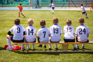 Kid's Sitting on a Soccer Bench