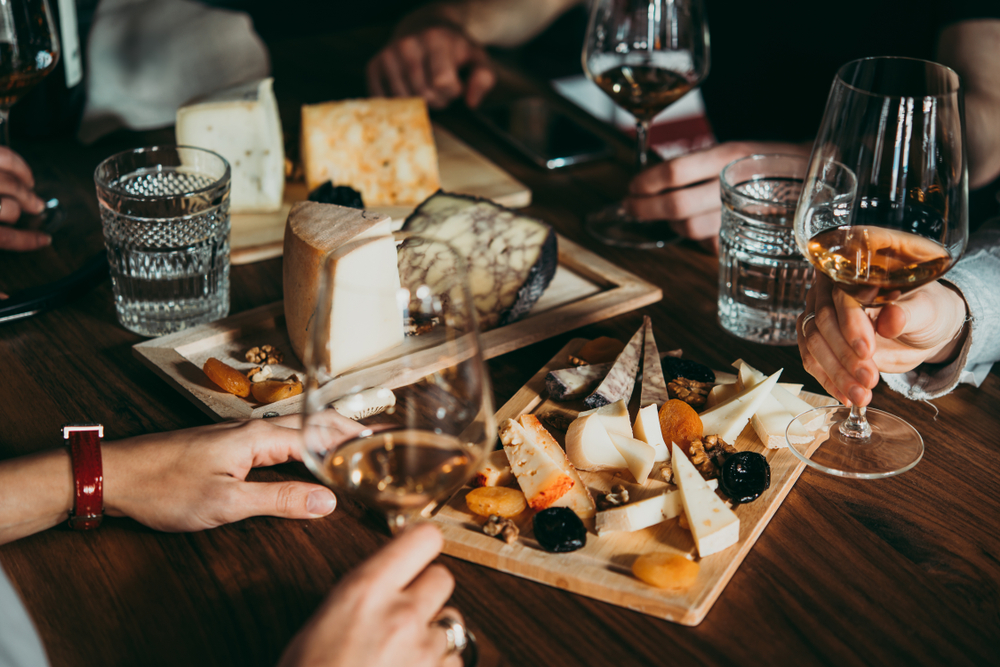 Friends Holding Wine Glasses Over Some Cheeseboards